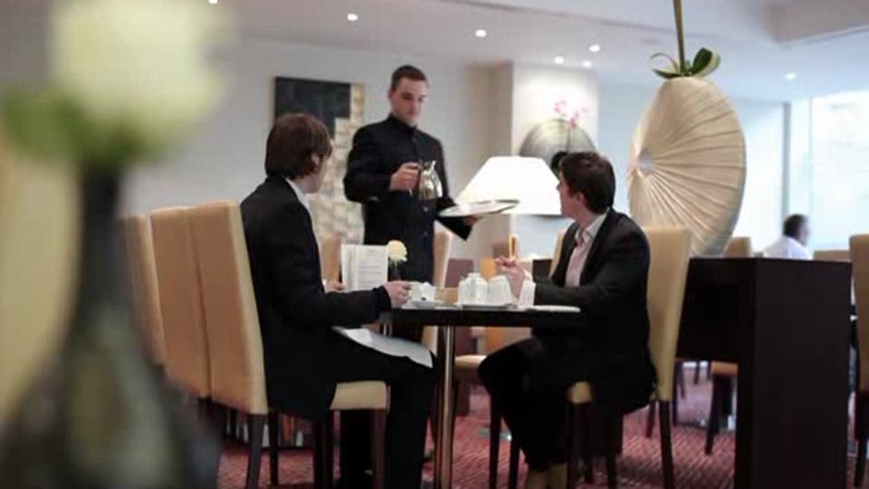 Restaurantfachmann bedient Gäste